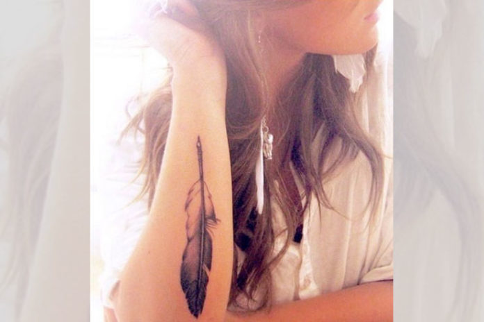 Elbow pointing feather tattoo