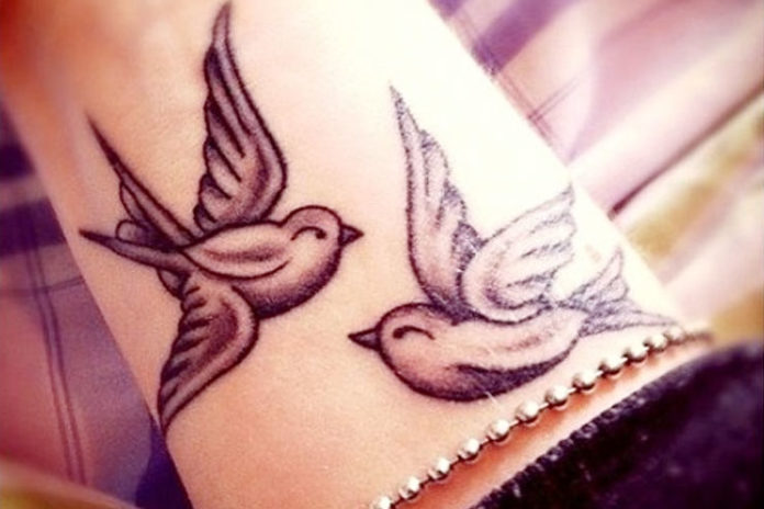 Two birds on wrist tattoos