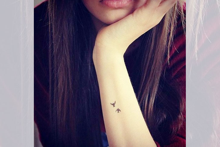 Tiny bird tattoos on arm